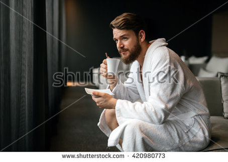Male model drinking coffee in robe